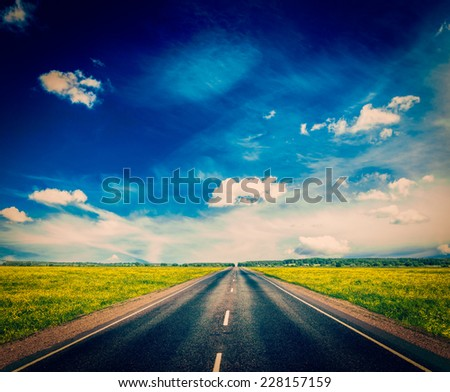 Vintage retro effect filtered hipster style image of travel concept background - road in blooming spring meadow - stock photo