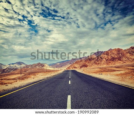 Vintage retro effect filtered hipster style travel image of Travel forward concept background - road in Himalayas with mountains and dramatic clouds. Ladakh, Jammu and Kashmir, India - stock photo