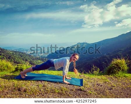 Vintage retro effect hipster style image of woman doing Hatha yoga asana Kumbhakasana plank pose  outdoors in mountains - stock photo