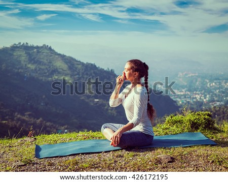 Vintage retro effect hipster style image of woman practices pranayama yoga breath control in lotus pose padmasana outdoors in Himalayas in the morning on sunrise. Himachal Pradesh, India - stock photo