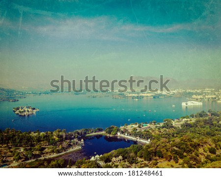 Vintage retro hipster style travel image of aerial view of Lake Pichola with Lake Palace (Jag Niwas) and Jag Mandir (Lake Garden Palace) with grunge texture overlaid.  Udaipur, Rajasthan, India - stock photo