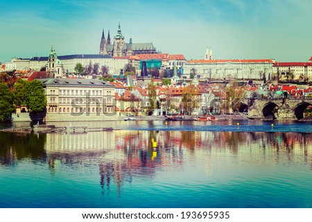 Vintage retro hipster style travel image of  Charles bridge over Vltava river and Gradchany (Prague Castle) and St. Vitus Cathedral - stock photo