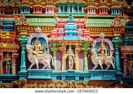 Vintage retro hipster style travel image of Shiva and Parvati on bull images. Sculptures on Hindu temple gopura (tower). Menakshi Temple, Madurai, Tamil Nadu, India - stock photo