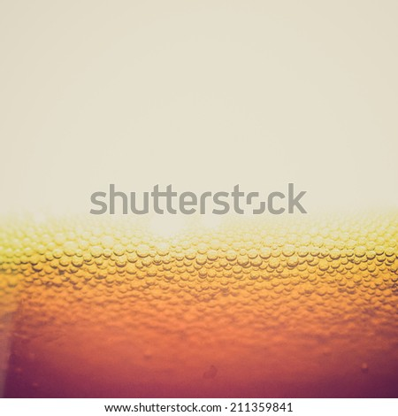 Vintage retro looking Beer foam in a glass, with copy space - stock photo