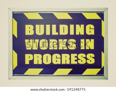 Vintage retro looking Building works in progress sign isolated over white