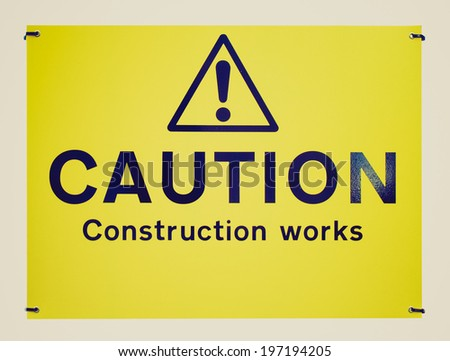 Vintage retro looking Caution construction works sign isolated on white