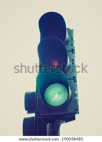 Vintage retro looking Green traffic light semaphore isolated over white background - stock photo