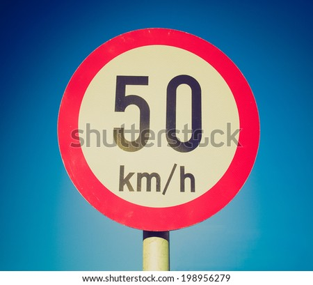 Vintage retro looking Traffic speed limit sign over blue sky - stock photo