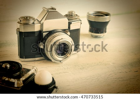 Vintage, retro SLR camera and accessories on wood surface, computer effect for retro feel