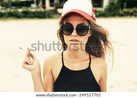Vintage retro style textured with scratches and grain closeup outdoor summer fashion lifestyle portrait of pretty blonde woman in hat smoking cigarettes  - stock photo