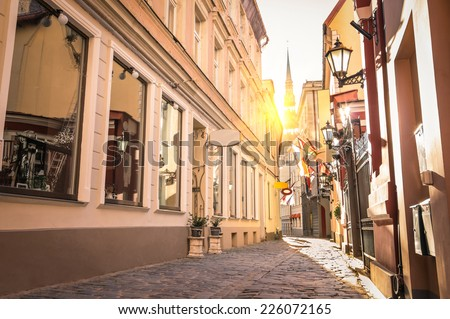 Vintage retro travel image of a narrow medieval street in old town Riga at sunset - Latvia - European capital of culture 2014 - stock photo