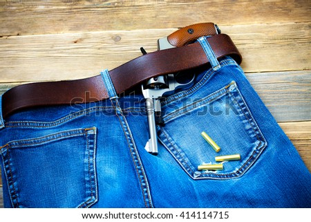 vintage revolver in his leather belt of blue jeans - stock photo