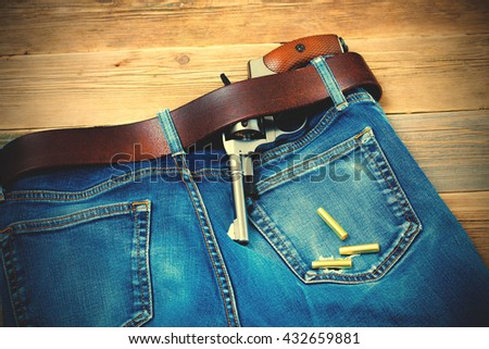 vintage revolver in his leather belt of blue jeans. instagram image filter retro style - stock photo