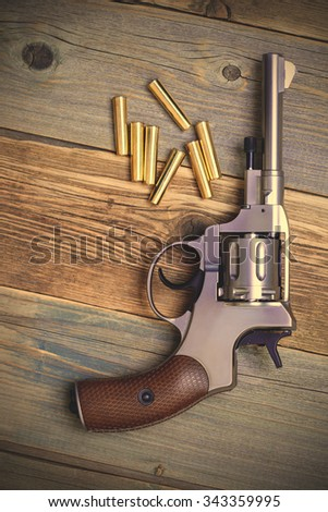 Vintage revolver nagant with a rotating drum and the seven golden cartridges on textured old boards. instagram image filter retro style - stock photo