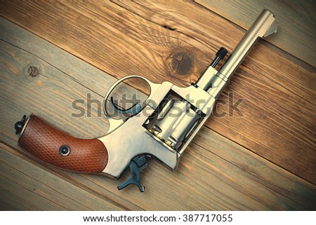 Vintage revolver nagant with a rotating drum on textured old boards. instagram image filter retro style - stock photo