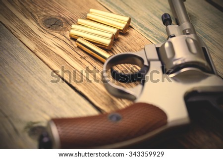 vintage revolver with cartridges on the surface of an ancient wooden table. Shallow depth of field. instagram image filter retro style - stock photo