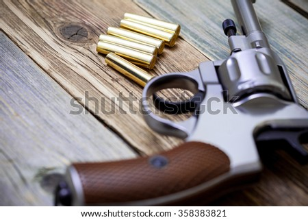 vintage revolver with cartridges on the surface of an ancient wooden table. Shallow depth of field - stock photo