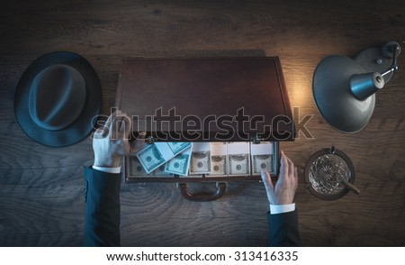 Vintage rich businessman's desk holding a briefcase filled with dollar packs, top view - stock photo