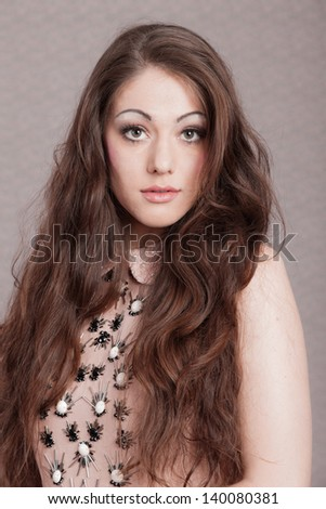Vintage romantic fashion woman with long hair. Wearing pink dress. Flower wallpaper. - stock photo