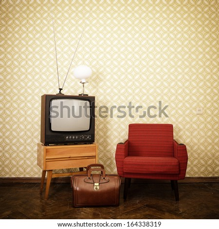 Vintage room with old fashioned armchair, retro tv, lamp and bag over obsolete wallpaper. Toned - stock photo
