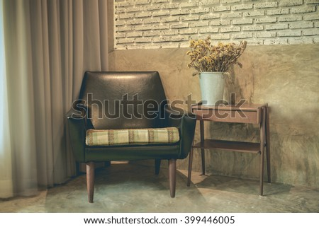 Vintage room with Old plaster walls and old fashioned armchair and a bookshelf with a vase of dried flowers adorn the room. - stock photo
