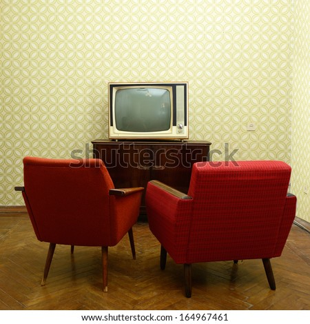 Vintage room with two old fashioned armchairs and retro tv over obsolete wallpaper - stock photo