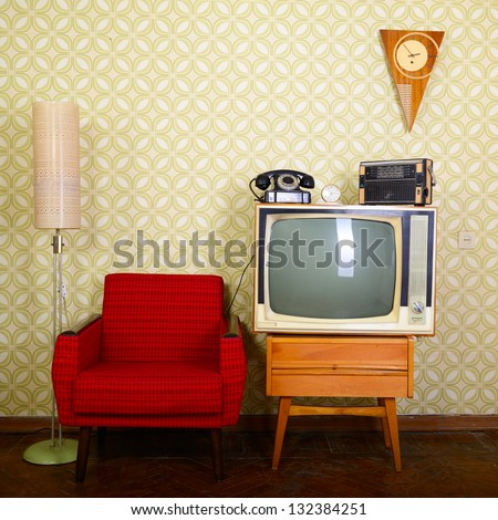 Vintage room with wallpaper, old fashioned armchair, retro tv, phone, clocks, radio player and standart lamp - stock photo