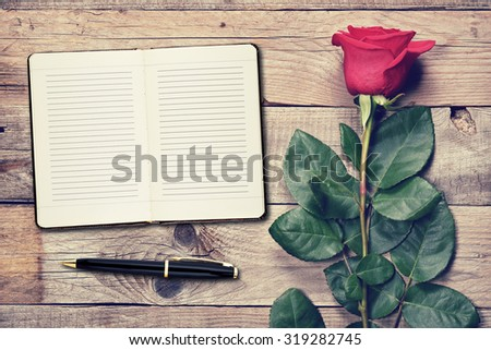 Vintage rose and diary on wooden background - stock photo