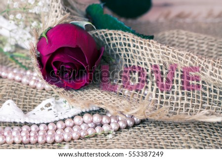Vintage Rose and small flowers on burlap background with Love in the middle
