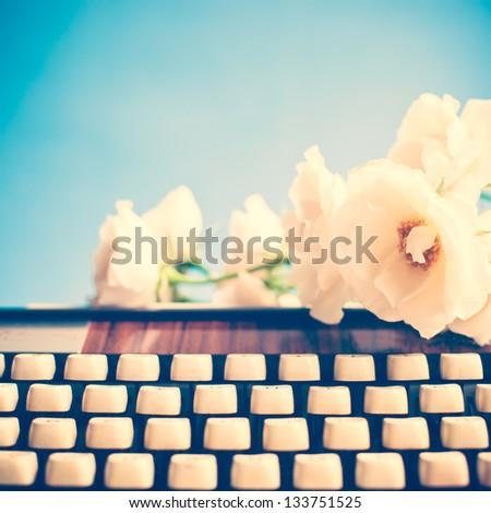 Vintage roses and typewriter - stock photo