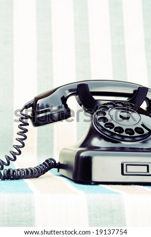 Vintage rotary phone on stripy background