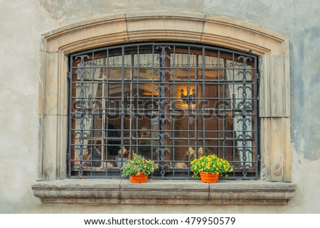 Vintage rounded window with metal grid and flower decor. Historical city elements Classic european architecture Postcard concept Travel inspiration Luxury estate background Vintage effect