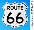 vintage route 66 sign against a vibrant blue sky background - stock photo
