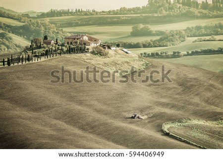Vintage rural landscape with tractor operating on the field, farmland