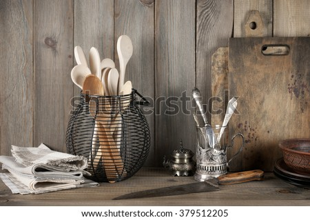 Vintage rustic kitchen still life: silver glass holder with cutlery, wire basket with wood spoons, ceramic dishware, towels and cutting boards against vintage wooden background.