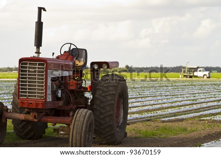 vintage rusty farmland equipment with farm backdrop - stock photo