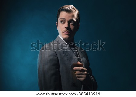 Vintage 1940s fashion man in suit and tie holding glass of whiskey against blue wall.