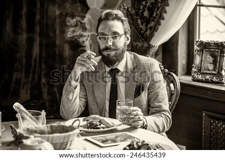 Vintage 1900's fashion man with a beard and curled mustache, smoking a cigar during dinner at the restaurant. Photo toned in sepia, stylized retro shoot. - stock photo