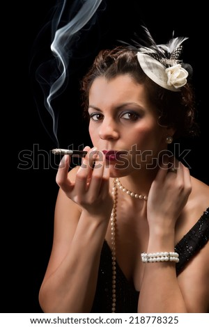Vintage 1920s lady smoking a cigarette with a mouthpiece - stock photo