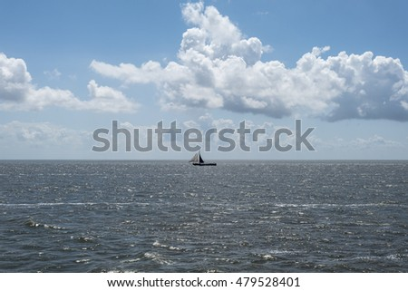 Vintage Sail boats waddenzee against blue cloudy sky