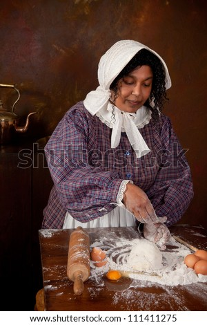 Vintage scene of a colonial woman kneading dough in an antique kitchen - stock photo