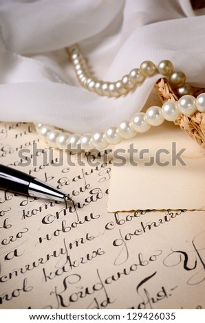 vintage scene. Pen on the letter with some jewelry - stock photo