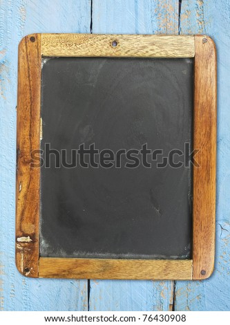 vintage school blackboard on painted wooden wall, free copy space - stock photo