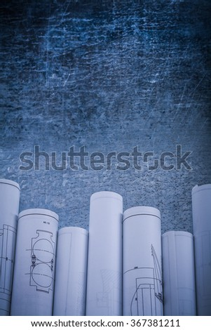Vintage scratched shiny metallic background with rolled blueprints copy space image construction concept. - stock photo