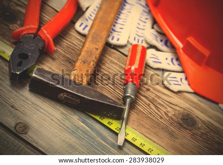 Vintage screwdriver, an old hammer, pliers, construction helmet, protective gloves and a measuring tape on old boards. instagram image filter retro style - stock photo