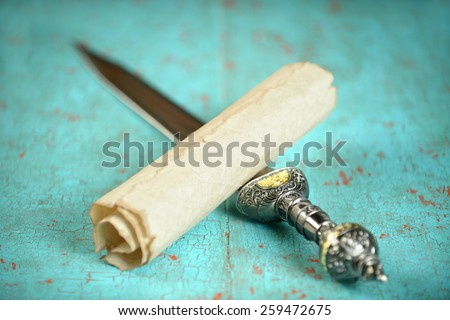 Vintage scroll and Roman sword on old table - Focus on scroll - stock photo
