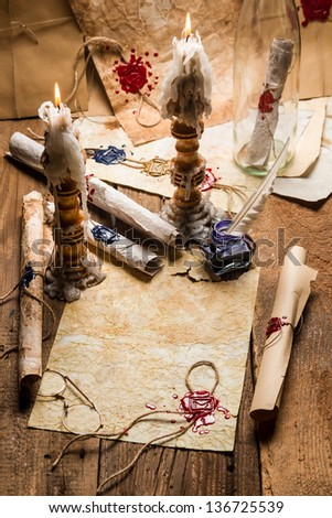 Vintage scrolls and candles are the old scribe's workplace - stock photo