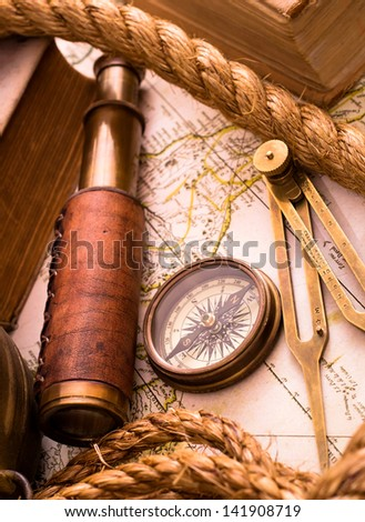 Vintage sea adventure concept. Medieval map, telescope and compass - stock photo