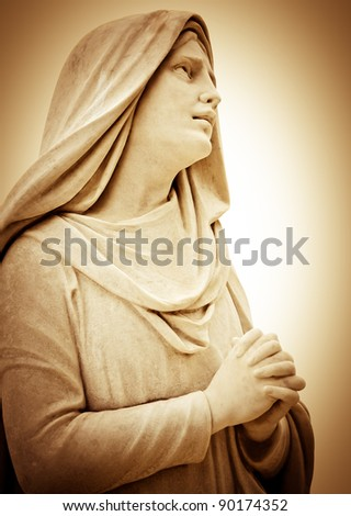 Vintage sepia image of a suffering religious woman praying - stock photo