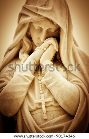 Vintage sepia image of a suffering religious woman with a crucifix - stock photo
